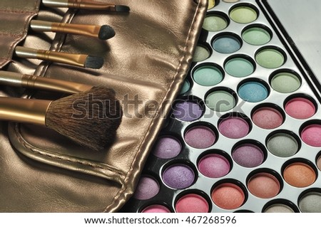 Colorful eye shadows palette with professional make-up brush. Make-up background