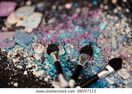 colorful eyeshadow powders and make-up brushes - stock photo