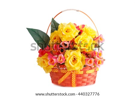 Colorful fabric roses in wicker basket isolated on white background.