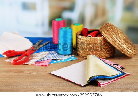 Colorful fabric samples and wicker basket of threads on wooden table and light blurred background - stock photo