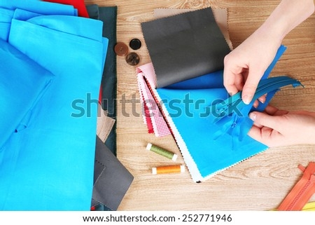 Colorful fabric samples and zipper in female hands on wooden table background - stock photo