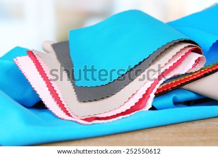 Colorful fabric samples on wooden table and light blurred background - stock photo