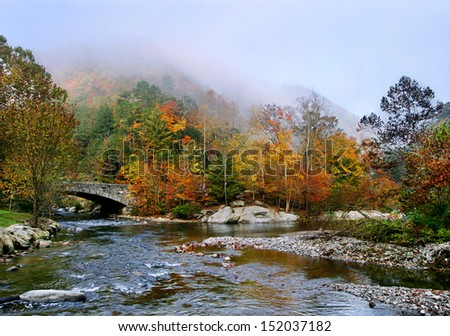 Colorful Fall Foliage And The Fog Descending At The Confluence Of Cedar Creek And Little River During Autumn In The Great Smoky Mountains National Park, Tennessee, USA - stock photo