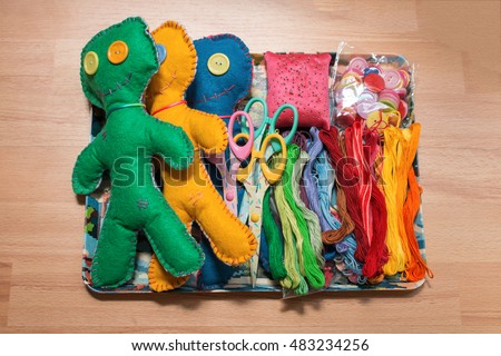 Colorful Felt Dolls with threads, scissors and buttons.