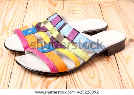 colorful female low-heeled sandals on a light wooden background