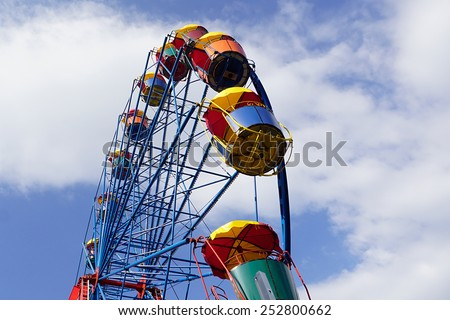 Colorful ferris wheel with cloudy blue sky at background  - stock photo
