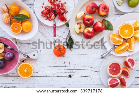 Colorful festive assortment of purple, red and orange fruit background in bowls. Lime, pomegranate, tangerine, orange, mandarin, apple, plum, grapefruit, lime sliced above white rustic tabletop. - stock photo
