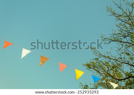 colorful festive bunting flags against a blue sky background in retro and vintage tone - stock photo