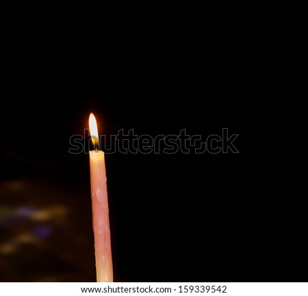 Colorful festive candle on dark background. Sunlight filtered through the stained glass window reflected on the candles and on the floor. - stock photo