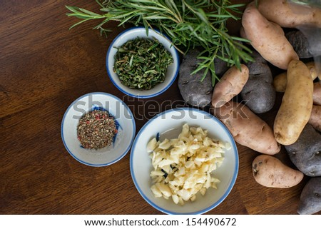 Colorful fingerling potatoes spilling out of a bag against fresh rosemary.  There are also 3 bowls filled with fresh minced garlic, pepper and chopped rosemary. - stock photo