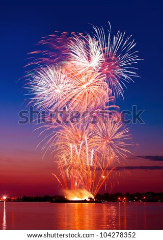 Colorful firework in a night sky, reflection in water - stock photo