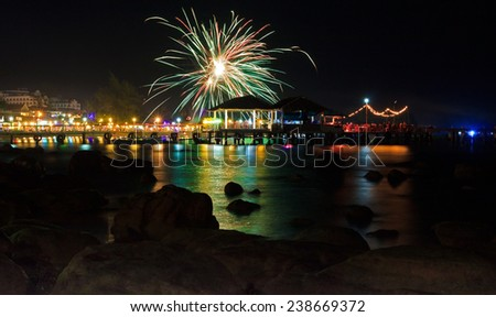 Colorful fireworks at pier in Sihanoukville, Cambodia at night with reflection in the water and silhouettes of stones at foreground - stock photo