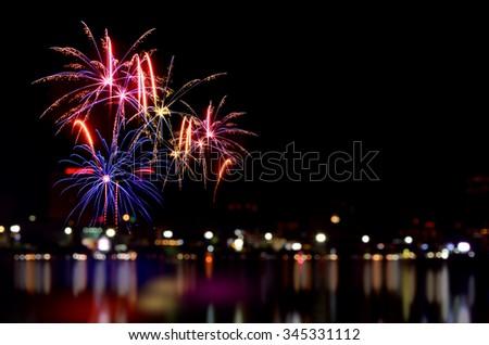Colorful fireworks celebration and the city night light background. - stock photo