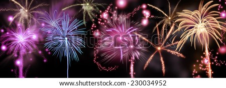 Colorful fireworks display of rockets bursting in a shower of fiery trails and sparks in a night sky to celebrate a festival or holiday such as New Year or Day of Independence - stock photo