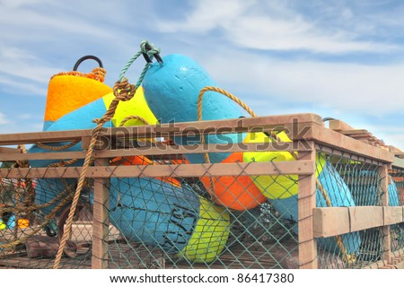 Colorful fisherman buoys laying in a lobster trap on a wharf in Prince Edward Island, Canada. - stock photo