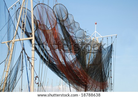 colorful fishing traps drying on a trawler in sun and wind under a clear blue sky - stock photo