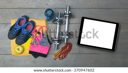 colorful fitness equipment and blank digital tablet on gym floor - stock photo