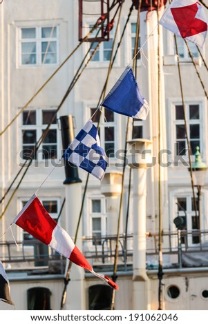 Colorful flags on old sailing boat - stock photo