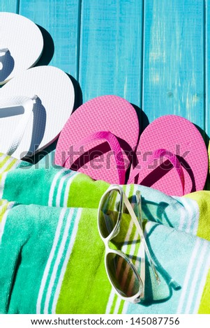 Colorful flip flops by a swimming pool. - stock photo