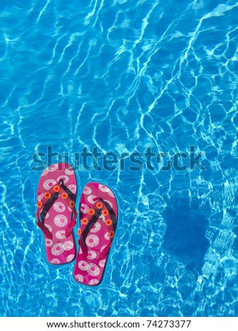 colorful flip-flops floating in a swimming pool, holiday concept - stock photo