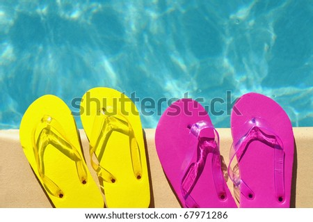 Colorful flip flops on the edge of a swimming pool - stock photo