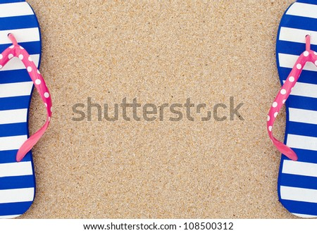 Colorful flipflop pairas a frame on beach sand - stock photo