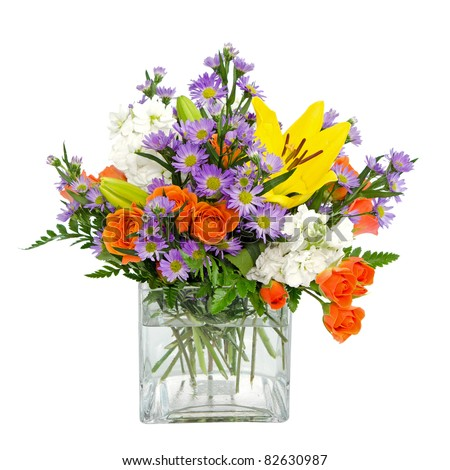 Colorful flower arrangement centerpiece  in square glass vase with roses, daisies and llilies isolated on white - stock photo