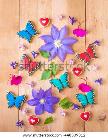 Colorful flowers and homemade butterfly shaped cookies floral composition on cedar wood table.