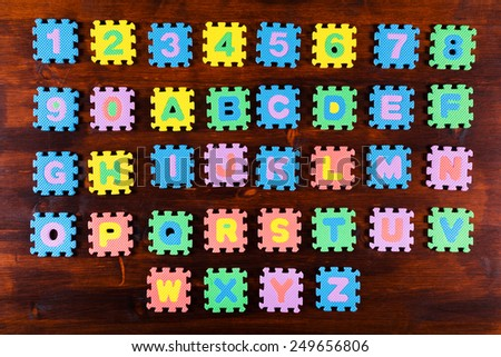 Colorful foam puzzle letters on wooden background, education concept - stock photo
