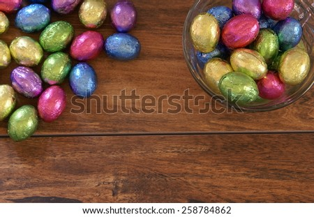 Colorful foil wrapped Easter egg shaped chocolate candy on a wood plank background with extra room for your text and images. - stock photo