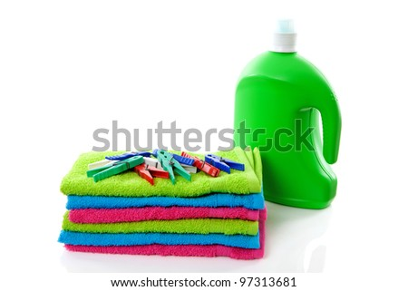 colorful folded towels, pegs and bottle over white background