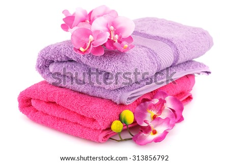 Colorful folded towels with flowers isolated on white background.
