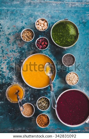 Colorful food collage. Colorful smoothie bowl recipe with super goods bowls and honey jar. Blend vegan food, dried seeds and grains. Rustic colorful composition. - stock photo
