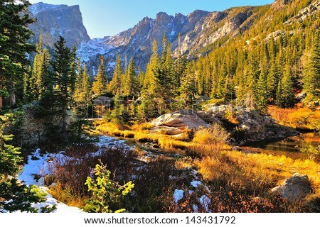 Colorful forest in Rocky Mountain National Park in fall with snow and mountains in background, Colorado, USA - stock photo