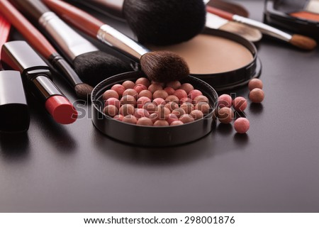 Colorful frame with various makeup products on black texture background. Selective focus.  - stock photo