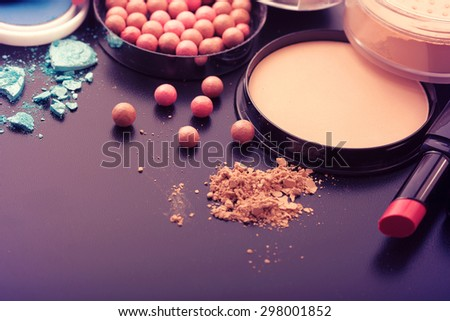 Colorful frame with various makeup products on black texture background. Selective focus, color toning. - stock photo