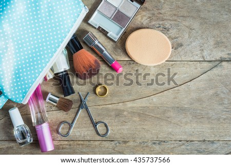 Colorful frame with various makeup products on wooden background with copy space, bag, lipstick ,powder, perfume, scissors, fingernail paint, brush. top. The concept cosmetics makeup, beauty, Travel. - stock photo