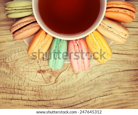 Colorful French Macaroon with Cup of Tea on wooden. Top View - stock photo