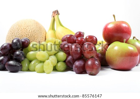 Colorful fresh fruits like grapes, cantaloupe,apples,and bananas on a white background - stock photo