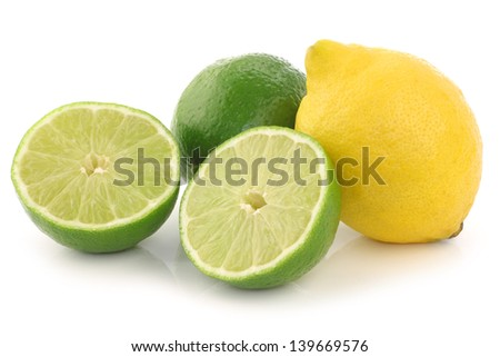 colorful fresh lime and lemon fruit and a cut one on a white background - stock photo