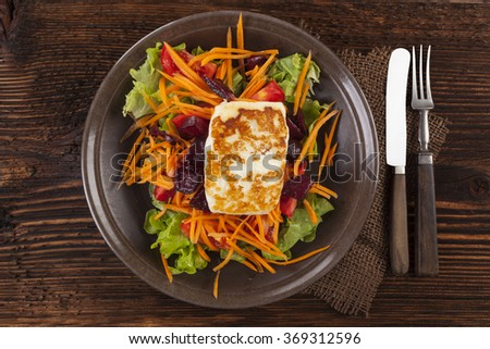 Colorful fresh salad with grilled halloumi cheese with on plate on wooden table, top view. Culinary delicious vegetarian eating, mediterranean style. - stock photo
