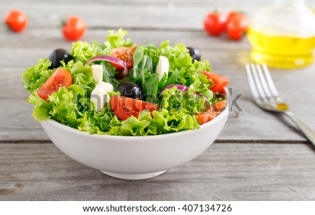 colorful fresh vegetable salad with mozzarella in a white deep bowl closeup on a wooden table. Focus on the tomato - stock photo