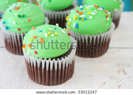 Colorful frosting on chocolate cupcakes shot at an angle. Background is an old wood white table with room for your text. - stock photo