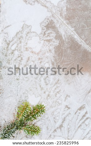 Colorful frozen window with green branch of fir tree with ice and snowflakes - stock photo