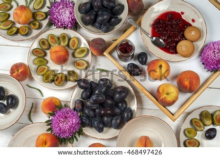 Colorful fruit set of purple, red and orange fruit background in bowls. Plum, peaches, watermelon sliced above white rustic tabletop.