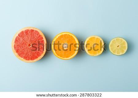 Colorful fruits in row on blue background. Grapefruit, orange, lemon and lime - stock photo