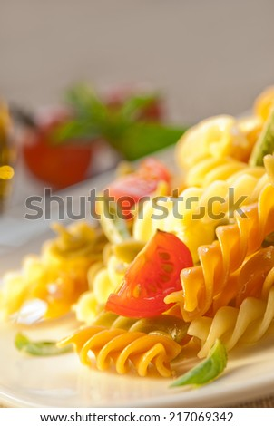 Colorful fusilli pasta with tomato and basil