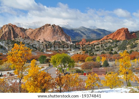 Colorful Garden of the Gods Park near Colorado Springs after a snow with golden leaved trees and partially cloud  covered Pikes Peak - stock photo