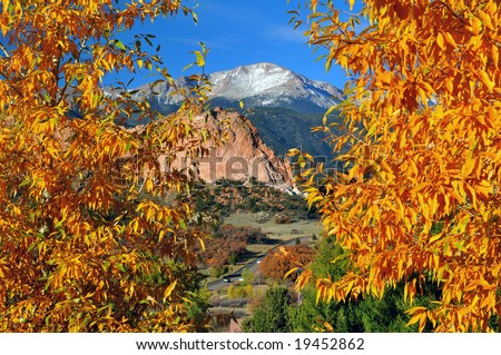 Colorful Garden of the Gods Park near Colorado Springs, Colorado with golden leaved trees and snow covered Pikes Peak - stock photo