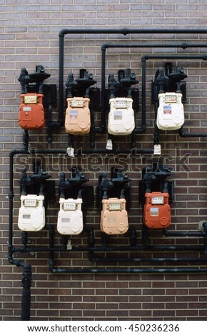 colorful gas meters on brick wall - stock photo
